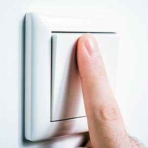 Schaltzyklen: Mann betätigt Lichtschalter mit Zeigefinger
